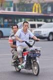 Uomini sulla e-bici nel centro urbano, Pechino, Cina Fotografia Stock