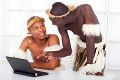 Uomini tribali che imparano calcolatore Immagine Stock Libera da Diritti