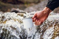 Uomini turistici portando una tazza del metallo contro lo sfondo dei fiumi vaghi immagine stock libera da diritti