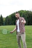 Uomo in abbigliamento casual che gioca il gioco in parco, concetto di volano di estate Immagini Stock