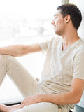 Uomo in abbigliamento casual che si siede sul davanzale Immagini Stock Libere da Diritti