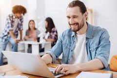 Uomo abile ambizioso che per mezzo del suo computer portatile mentre studiando Fotografia Stock Libera da Diritti