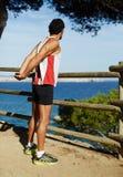 Uomo in abiti sportivi, allungamento dopo avere corso all'aperto nelle montagne Il tipo ha eseguito la distanza fermata per esami Fotografie Stock