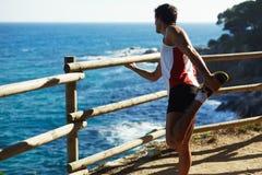 Uomo in abiti sportivi, allungamento dopo avere corso all'aperto nelle montagne Il tipo ha eseguito la distanza fermata per esami Fotografia Stock
