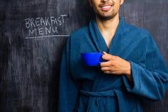 Uomo in abito accanto al menu della prima colazione sulla lavagna Fotografia Stock