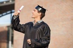 Uomo in abito di graduazione che esamina certificato sopra Immagini Stock Libere da Diritti