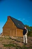 Uomo accanto alla casa nel campo Fotografia Stock Libera da Diritti