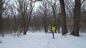 Uomo adatto atletico che si scalda durante le precipitazioni nevose nella foresta di inverno con spazio libero stock footage