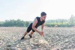 Uomo adatto che fa spinta-UPS d'applauso durante l'allenamento di esercizio di allenamento sulla spiaggia di estate Fotografia Stock