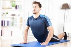 Uomo adatto che fa stampa sull'esercizio su una stuoia di forma fisica Immagini Stock