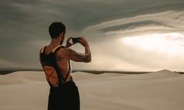 Uomo adatto che prende le immagini del cielo nuvoloso in deserto Fotografia Stock