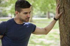 Uomo adatto dei giovani che allunga nel parco con un orologio dell'inseguitore di forma fisica Fotografie Stock