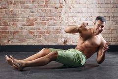 Uomo adatto dei giovani che si esercita in una palestra sul vecchio fondo dei mattoni rossi Fotografie Stock