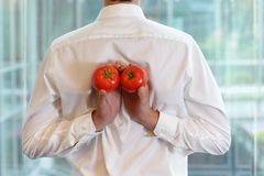 Uomo adatto di affari con i pomodori come spuntino healhy Fotografie Stock