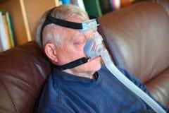 Uomo addormentato con il copricapo di CPAP immagine stock