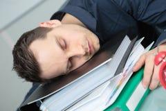Uomo addormentato sulle cartelle della pila Fotografia Stock Libera da Diritti