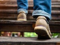 Uomo adulto che cammina sulle scale di legno Muovere in avanti concetto immagini stock libere da diritti