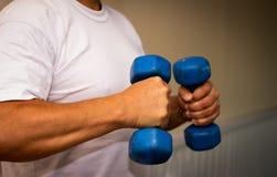 Uomo adulto che fa esercizio nella palestra Uomo con i piccoli pesi blu Concetto di benessere e di salute fotografie stock libere da diritti