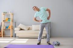 Uomo adulto che fa gli esercizi a casa Immagine Stock