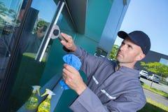 Uomo adulto che lava l'automobile sporca della finestra Fotografia Stock