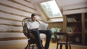 Uomo adulto che pratica il surfing Internet sul computer portatile in una sedia archivi video