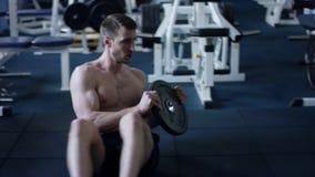 Uomo adulto che si esercita con i pesi in una palestra stock footage