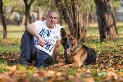 Uomo adulto che si siede all'aperto con il suo pastore tedesco Fotografie Stock