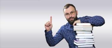 Uomo adulto della barba dello studente con la pila di libro Immagine Stock