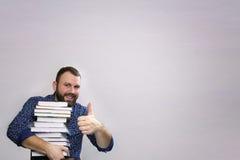 Uomo adulto della barba dello studente con la pila di libro in una biblioteca Fotografie Stock