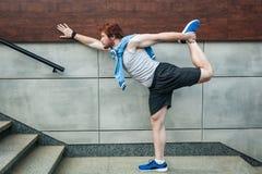 Uomo adulto della testarossa di sport di forma fisica giovane in abiti sportivi che fanno esercizio di forma fisica di yoga Immagini Stock