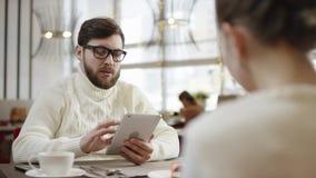 Uomo adulto e donna che si siedono dalla tavola in ristorante di lusso ed attimo di conversazione facendo uso dei dispositivi video d archivio