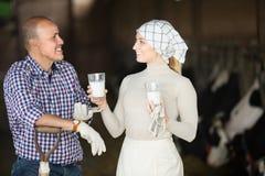 Uomo adulto e lavoratrici agricole che stanno con il latte Fotografia Stock Libera da Diritti
