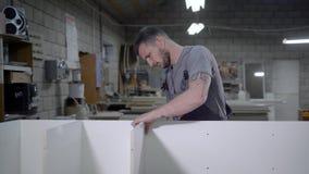 Uomo adulto lavorante nel supporto di fabbricazione uniforme con i pannelli bianchi in garage stock footage