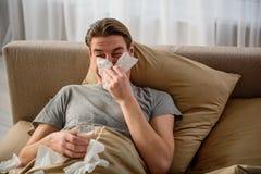 Uomo adulto malato che ha resto in camera da letto Immagine Stock