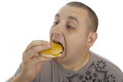 Uomo affamato con l'hamburger. Fotografia Stock
