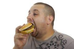 Uomo affamato con l'hamburger. Fotografie Stock