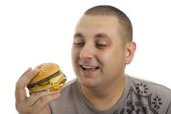 Uomo affamato con l'hamburger. Fotografie Stock Libere da Diritti