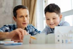 Uomo affascinante che dice suo figlio circa i benefici dei pannelli solari Immagini Stock