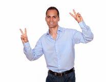 Uomo affascinante che sorride e vi che mostra il segno di vittoria Fotografia Stock
