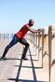 Uomo africano adatto che fa allungando allenamento alla passeggiata della spiaggia Immagine Stock Libera da Diritti