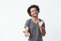 Uomo africano allegro che ascolta la musica in cuffie che ballano canto Fotografie Stock Libere da Diritti