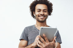 Uomo africano allegro in compressa sorridente della tenuta delle cuffie che esamina macchina fotografica Priorità bassa bianca immagini stock