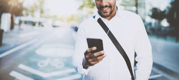 Uomo africano americano felice che per mezzo dello smartphone all'aperto Ritratto di giovane uomo allegro nero che manda un sms a Fotografia Stock Libera da Diritti