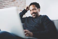 Uomo africano barbuto allegro che lavora al computer portatile mentre sedendosi sofà al suo Ministero degli Interni moderno Conce Immagine Stock