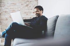 Uomo africano barbuto allegro che lavora al computer portatile mentre sedendosi sofà al suo posto moderno dell'ufficio Concetto d Immagine Stock