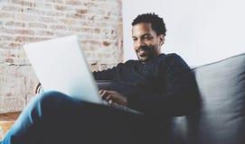 Uomo africano barbuto attraente che smling e che lavora al computer portatile mentre sedendosi sofà al suo Ministero degli Intern Fotografie Stock