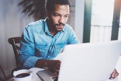 Uomo africano barbuto serio che lavora al computer portatile mentre spendendo tempo a casa Concetto della gente di affari che usa Immagine Stock Libera da Diritti