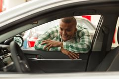 Uomo africano bello che sceglie nuova automobile alla gestione commerciale immagini stock libere da diritti