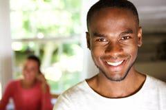 Uomo africano bello che sorride con una donna nel fondo fotografie stock libere da diritti
