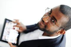 Uomo africano bello con il calcolatore del ridurre in pani Fotografia Stock Libera da Diritti